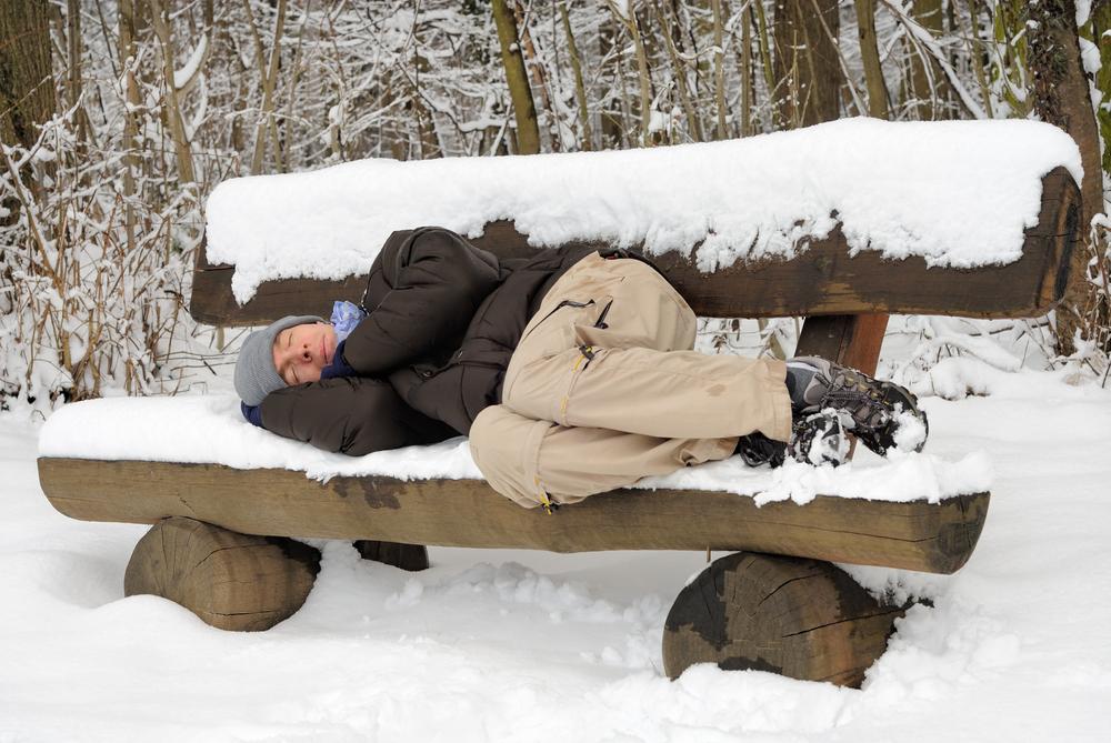 Спит на лавочке зимой в снегу
